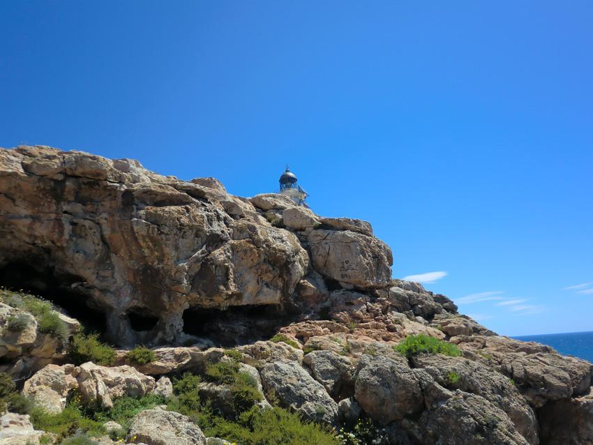 El Faro de Barbaria se asoma sobre las rocas, visto desde la Cova Foradada